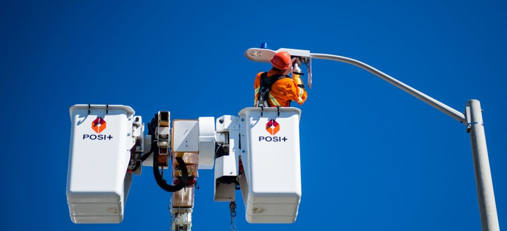 Worker in the field fixing street lights